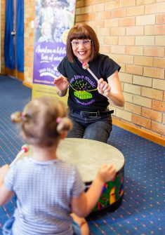 Teacher playing drum with kid in music class